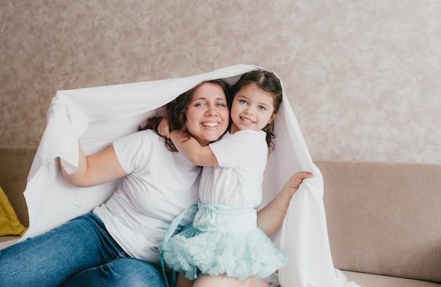 Счастливая маленькая девочка в легкой водолазке обнимает маму под белой простыней. любящая и заботливая мама Premium Фотографии