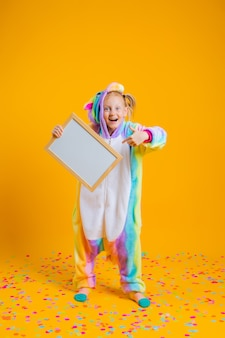 Счастливая маленькая девочка в кигуруми единорога держит пустую доску для текста на желтой стене