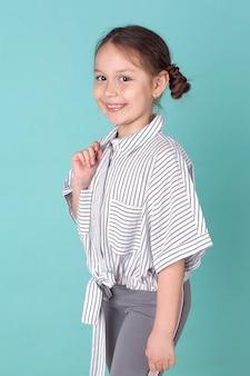 Счастливая маленькая девочка слушает музыку, стоя на синем фоне в студии.