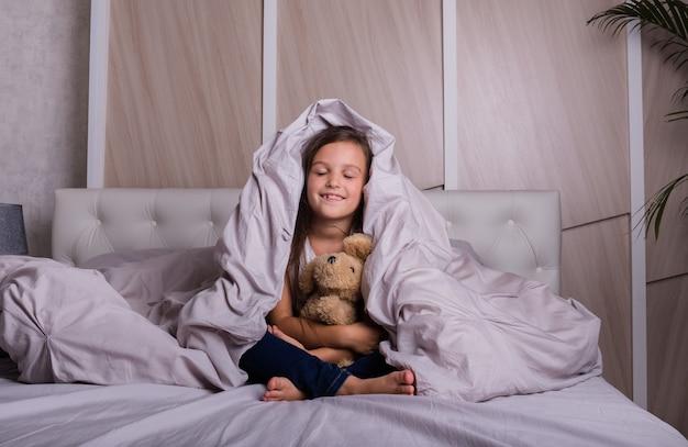 幸せな少女は目を閉じてぬいぐるみを抱きしめてベッドに座っています