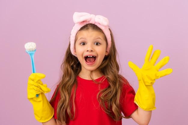 행복한 어린 소녀가 집을 깨끗하게 유지합니다. 고무 장갑과 스크럽 브러시.