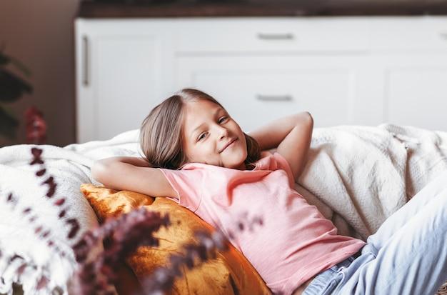 Счастливая маленькая девочка отдыхает на диване в гостиной.