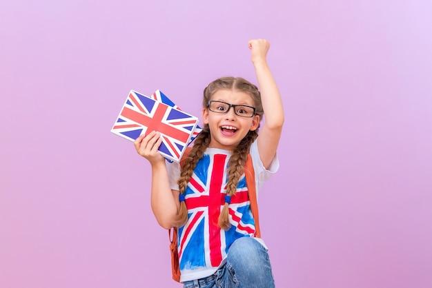 안경을 쓴 행복한 어린 소녀가 영어 책을 들고 손을 들어 올립니다.