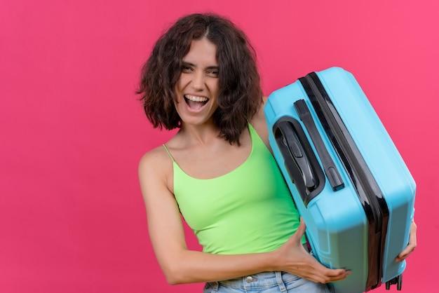Счастливая милая женщина с короткими волосами в зеленом топе показывает свой синий чемодан