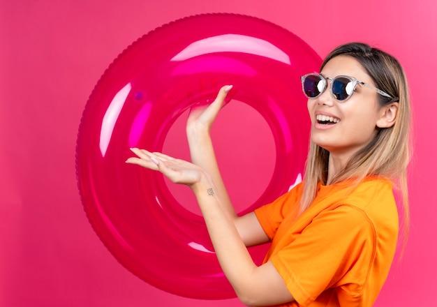 ピンクの壁にピンクのインフレータブルリングを保持しながら笑顔と見てサングラスをかけているオレンジ色のtシャツを着た幸せな素敵な若い女性