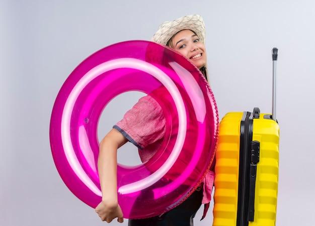 白い壁に黄色のスーツケースとインフレータブルリングを保持しながら赤いシャツと日よけ帽を身に着けている幸せな素敵な若い女性
