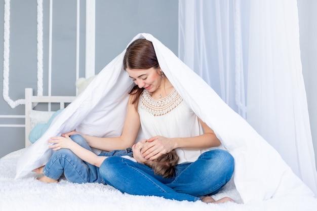행복하고 사랑하는 가족. 엄마와 아기 아들은 담요 아래 침대에 집에서 재생