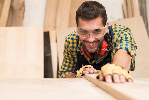 Счастливый мужской плотник поправляет деревянную доску в мастерской