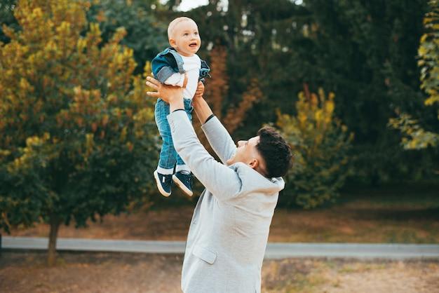 幸せな男が公園で赤ちゃんを抱いて