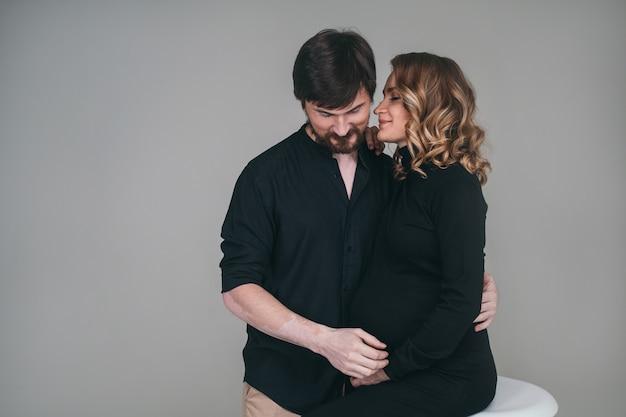 幸せな男は彼の妊娠中のガールフレンドの隣に立っています。愛情深い両親が赤ちゃんの誕生を待っています。夫は妊娠中の妻の胃を抱きしめます。