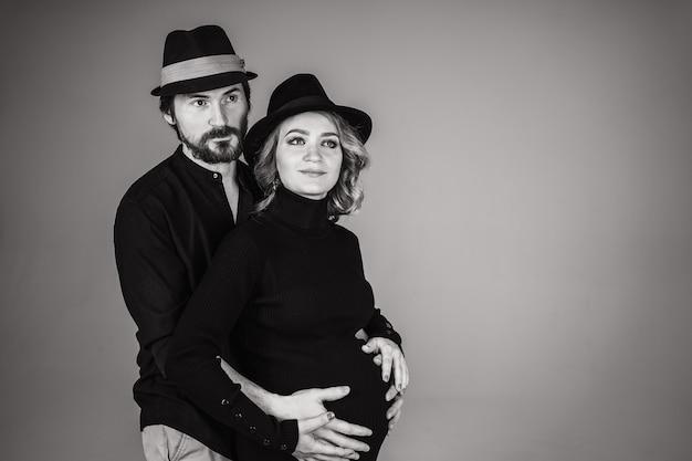 행복한 남자가 임신 한 여자 친구 옆에 선다. 사랑하는 부모가 아기의 탄생을 기다리고 있습니다. 남편은 임신 한 아내의 배를 껴안습니다.