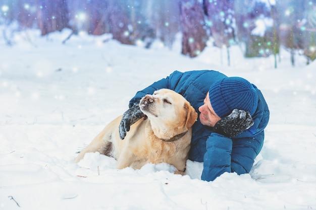 Счастливый человек с собакой лабрадора-ретривера, лежащей в снегу зимой. человек обнимает собаку