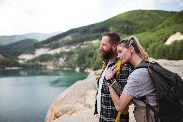 Счастливая зрелая пара в походе на летние каникулы, отдыхая на берегу озера.