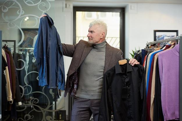 白髪とスポーティな体格の幸せな成熟した男は、衣料品店で2枚のシャツから選択しています。あごひげを生やした男性客は、ブティックでウールのスーツを着ています。
