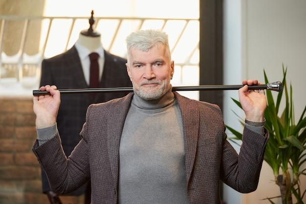 白髪とスポーティな体格の幸せな成熟した男は、衣料品店で彼の頭の後ろに両手でファイバーカーボン杖を持っています。あごひげを生やした男性客がブティックでスーツを着ています。