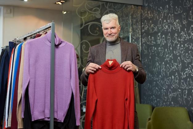 白髪とスポーティな体格の幸せな成熟した男は、衣料品店で赤いタートルネックのセーターを見せています。あごひげを生やした男性客は、ブティックでウールのスーツを着ています。