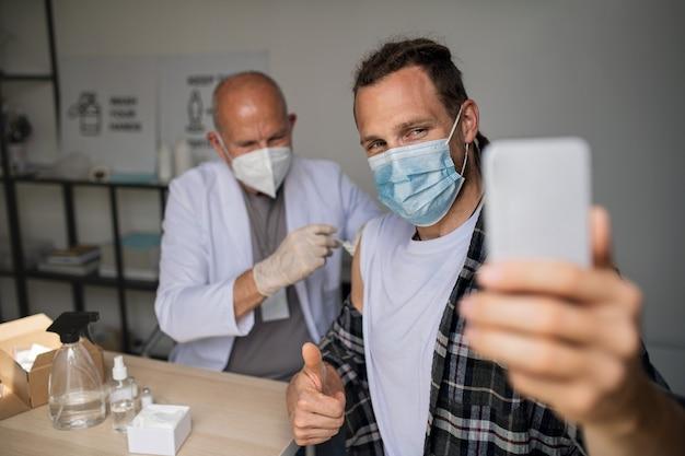 예방 접종을 받을 때 셀카를 찍는 행복한 중년 남성, 코로나바이러스 개념.