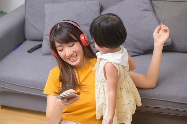 音楽を聴き、家でリラックスして幸せな母と娘