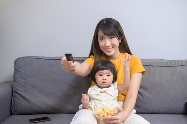 Счастливая мама и дочь смотрят фильм и отдыхают дома