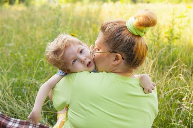 幸せな母親と障害児が公園の芝生に座って優しく抱きしめています。夏休み。障害。