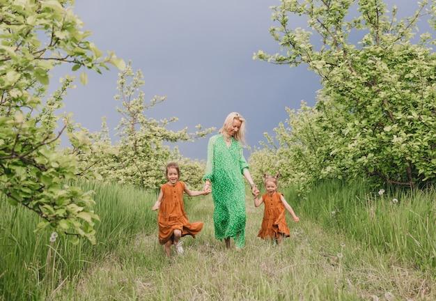 緑のドレスを着た幸せな母親は、雨の前に庭で2人の小さな娘と一緒に歩きます。家族の幸せと母親のケア