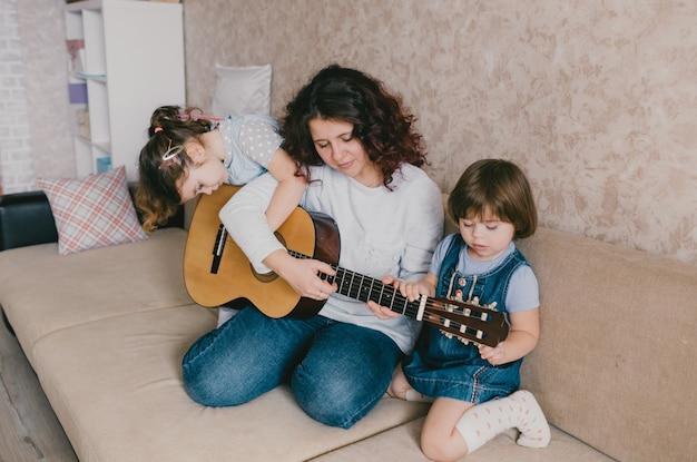 Счастливая мама учит двух своих маленьких дочерей игре на акустической гитаре.