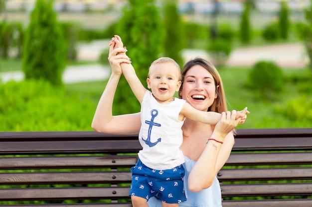 공원에서 아기를 안고 있는 행복한 엄마가 야외 벤치에 앉아 아기를 안고 즐거운 시간을 보내고 있습니다.