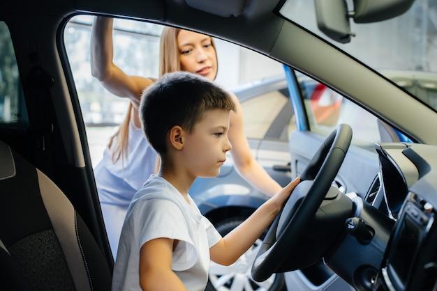 幼い息子と幸せな母親が自動車販売店で新しい車を選ぶ