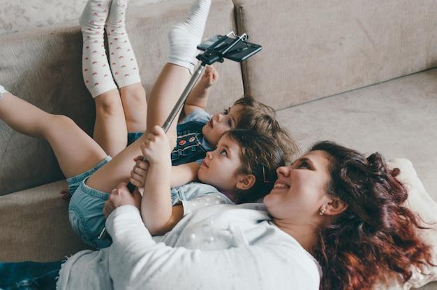 Счастливая мама с двумя маленькими дочерьми лежит на диване и фотографирует себя на телефон. делает селфи
