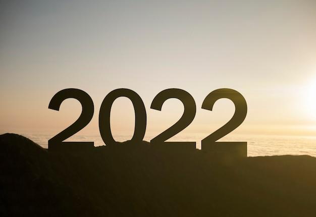 新しい成功と機会の日没のシンボルと山の頂上に新年あけましておめでとうございます