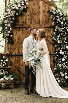Счастливая пара молодоженов позирует с деревянной аркой, украшенной цветами