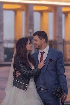 夜の街を歩く幸せな新婚夫婦。スタイリッシュな新郎新婦。結婚式のコンセプト