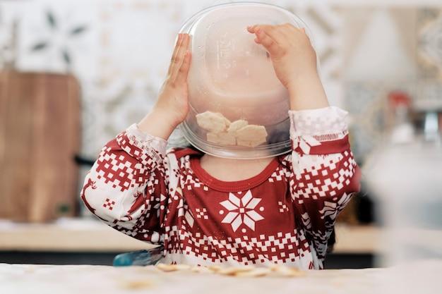 幸せな1歳の女の子がハイチェアの白いテーブルに座って、一人でボウルから食事をし、食べ物を楽しんでいます
