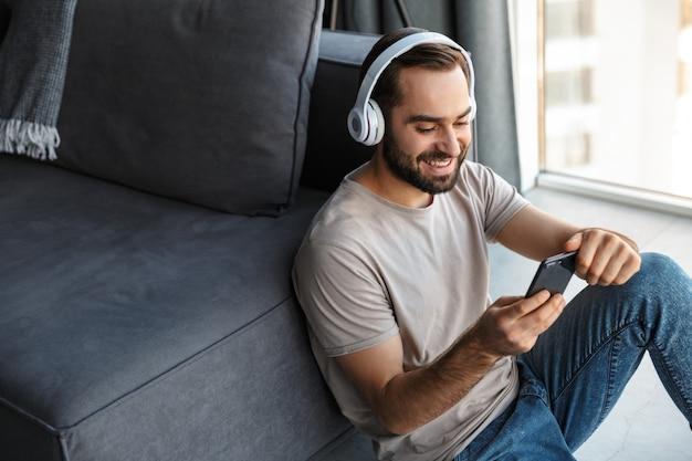 Счастливый оптимистичный молодой человек в помещении дома, слушая музыку в наушниках, сидит на полу в чате по мобильному телефону.