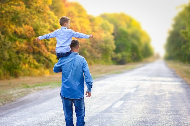 Счастливый родитель с ребенком в парке на природе путешествует по дороге
