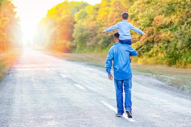 공원에서 자녀와 함께 행복한 부모가 자연 여행에 손을 뻗어 길을 따라갑니다.