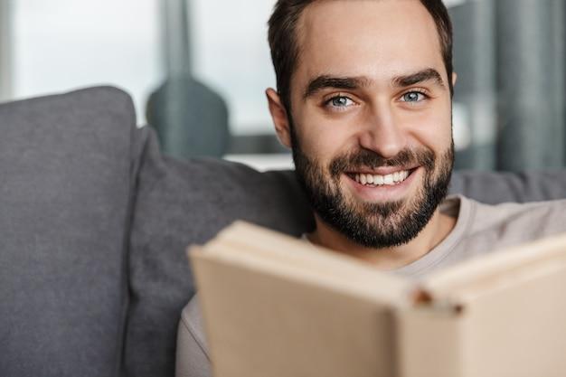 Счастливый позитивный молодой человек в помещении дома на софе, читая книгу.