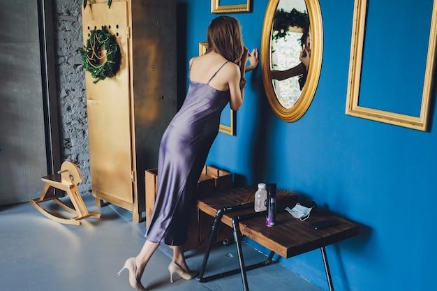 幸せな妊娠中の女性は、鏡の中の自分と生まれていない赤ちゃんの反射を愛情を込めて見ています