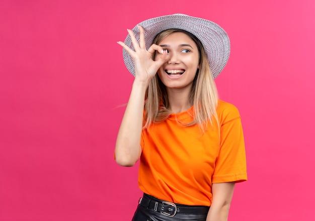 Счастливая симпатичная молодая женщина в оранжевой футболке в шляпе от солнца показывает жест `` ок '', глядя в сторону на розовой стене