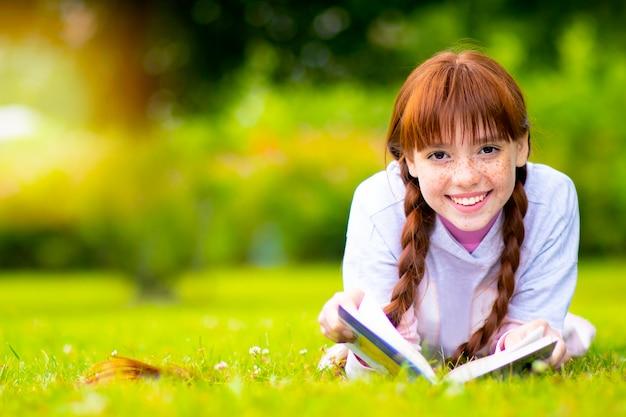 Счастливая рыжеволосая девочка с веснушками лежит и отдыхает на зеленой лужайке, читает книгу. самка улыбается за травой в парке. открытый, снаружи
