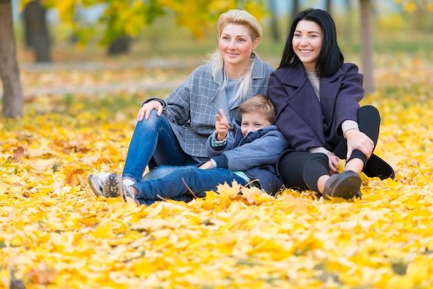 행복한 동성 여성 커플과 노란색 단풍과 함께 행복한 가족 테마의 그들의 아들.