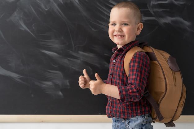 6-7歳の幸せな男子生徒がランドセルを持って黒板の近くの学校に立っています。彼は2本の親指でクラスを示しています。 9月1日。学校に戻る。男子生徒がシャツを着ています