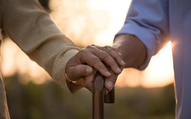 Счастливая пара старших, взявшись за руку, символ любви