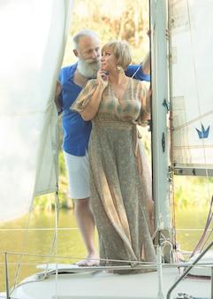 Счастливая старшая пара плавая и сидя за рулем парусника на озере.