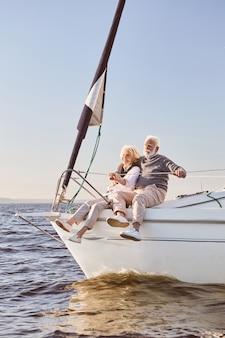 彼を抱き締める穏やかな青い海の男に帆船の横に座って話している幸せな年配のカップル