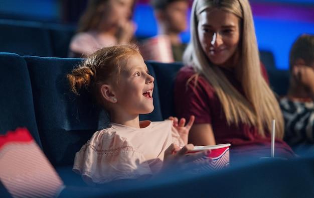 Счастливая маленькая девочка с мамой в кино, смотрят фильм.
