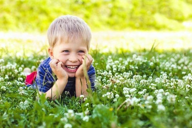 幸せな、笑顔の少年は緑の芝生の上に横たわっています。幸せな子供時代、夏とアウトドアレクリエーション
