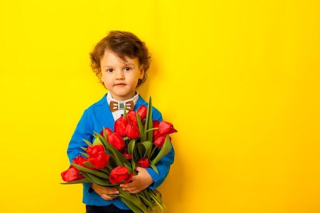 Счастливый улыбающийся ребенок держит огромный букет красных тюльпанов для матери на ярко-желтом фоне. подарок любимой маме от сына.