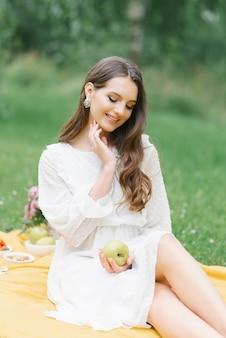 幸せな笑顔の女の子は彼女の手でリンゴを持って、街の外の夏のピクニックで黄色い毛布の上に座っています