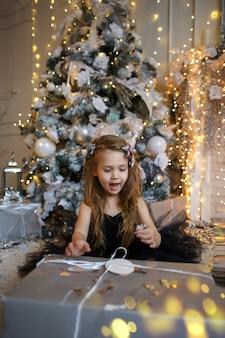 ゆるい髪の黒のエレガントなドレスで幸せな笑顔の女の子は、贈り物を開きます